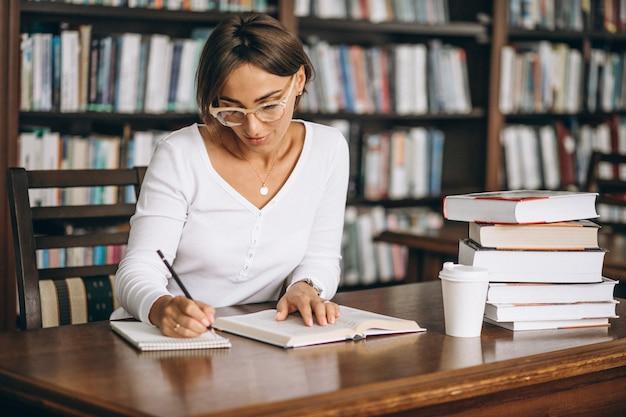 Donna dello studente che studia alla biblioteca e che beve caffè