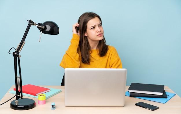 Donna dello studente che studia nella sua casa isolata sulla parete blu che ha dubbi