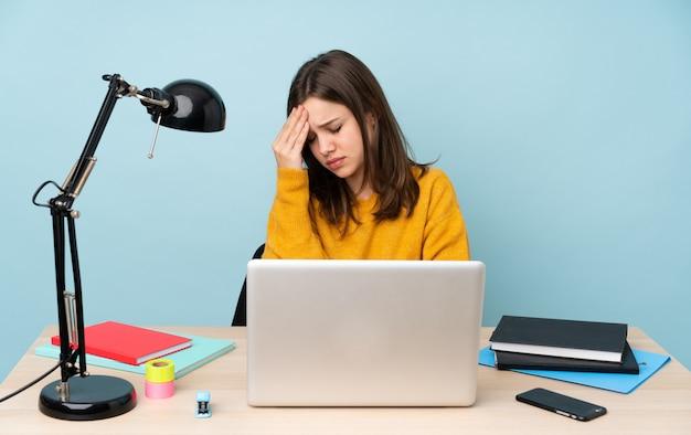 Donna dello studente che studia nella sua casa isolata sulla parete blu con l'emicrania