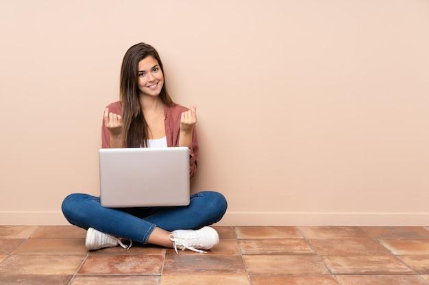 Donna dello studente dell'adolescente che si siede sul pavimento con un computer portatile che fa gesto dei soldi