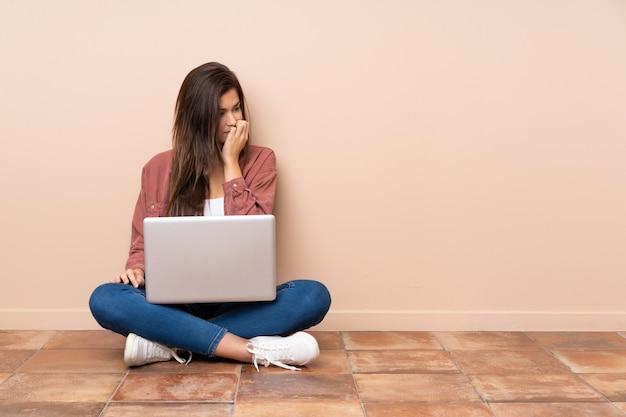 Donna dello studente dell'adolescente che si siede sul pavimento con un computer portatile che ha dubbi