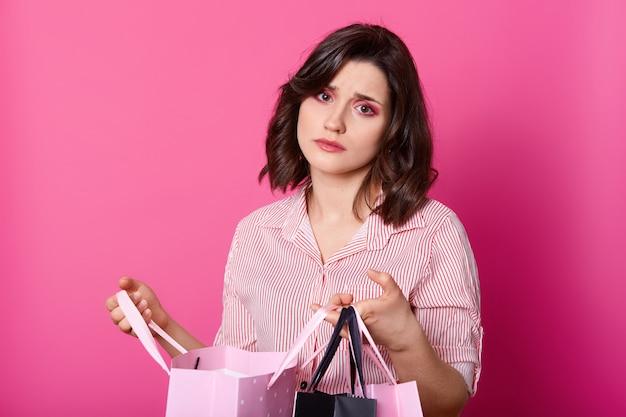 Donna delusa dai capelli scuri, indossa una camicetta rosa, tiene la borsa aperta. bella bruna sembra infelice, non piace l'acquisto.