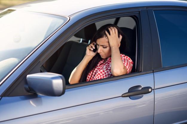 Donna delusa in camicia rossa alla guida di auto costose, parlando sullo smartphone durante la guida.