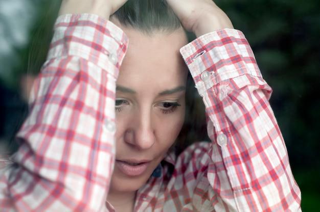 Donna depressa attraverso il vetro