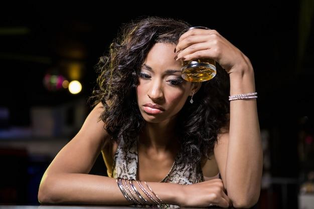 Donna depressa che beve whisky al bancone del bar nella barra