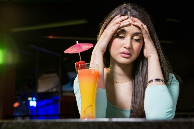 Donna depressa che ha bevanda del cocktail al contatore della barra nella barra