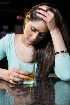 Donna depressa che mangia whiskey al contatore della barra nella barra