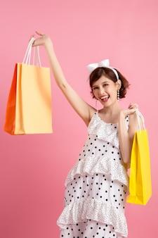 Donna di acquisto che tiene i sacchetti della spesa sul rosa