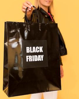 Donna di acquisto venerdì nero che tiene grande borsa