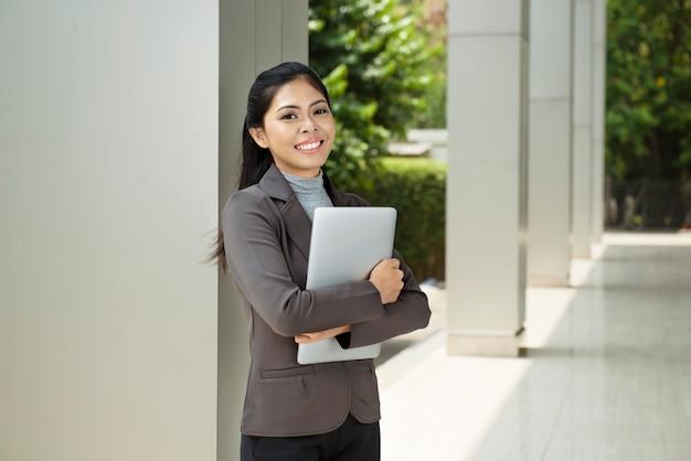 Donna di affari abbastanza asiatica con il computer portatile