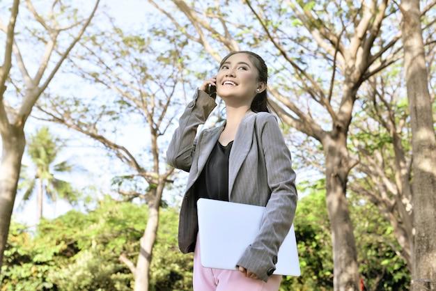Donna di affari abbastanza asiatica con il telefono ed il computer portatile