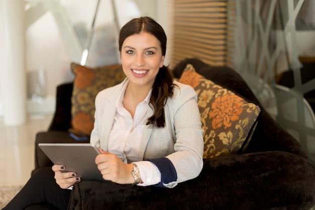 Donna di affari abbastanza giovane con la compressa digitale che si siede nella sala di attesa dell'ufficio