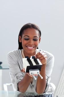Donna di affari afroamericana che tiene un titolare del biglietto da visita