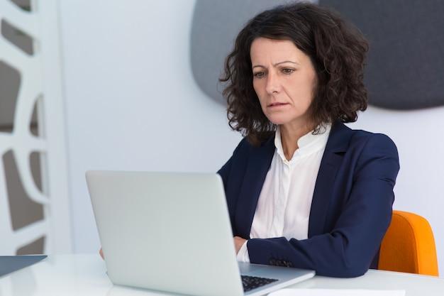 Donna di affari aggrottante le sopracciglia confusa che ottiene riguardo alle notizie