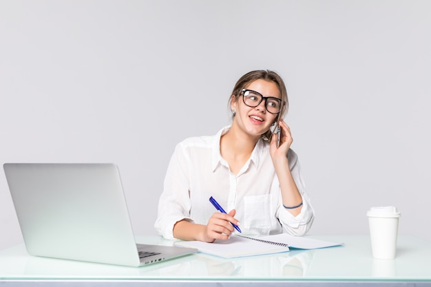Donna di affari al suo scrittorio funzionante con il computer portatile e il telefono parlante isolati su fondo bianco