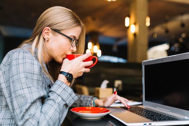Donna di affari alla moda con il computer portatile in caffetteria accogliente