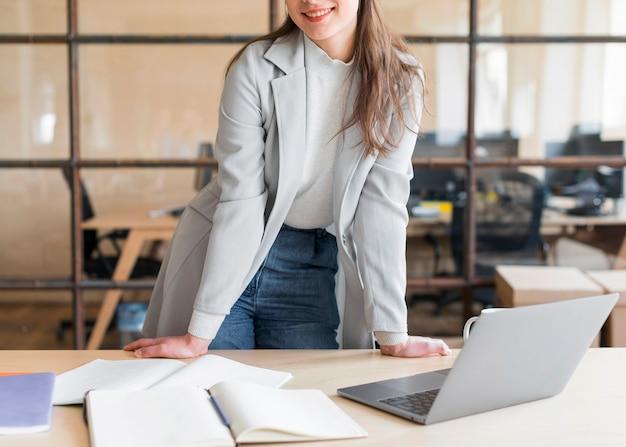 Donna di affari alla moda sorridente che si leva in piedi davanti al computer portatile