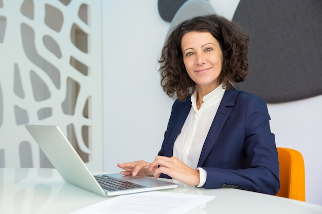Donna di affari allegra che per mezzo del computer portatile