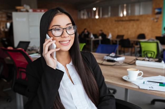 Donna di affari allegra che si siede e che parla sul telefono cellulare in ufficio