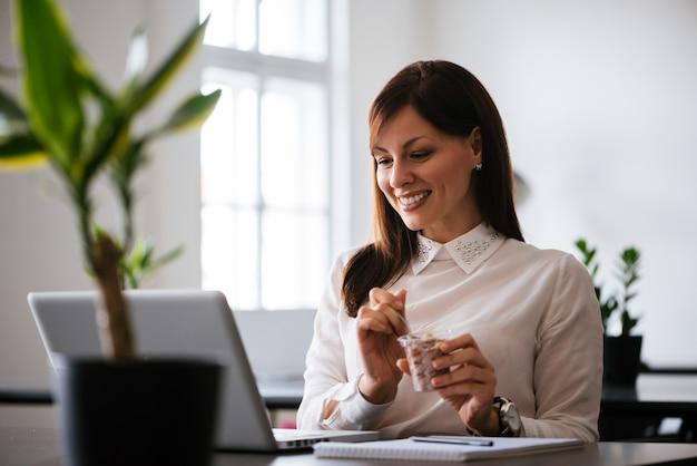 Donna di affari allegra che si siede nell'ufficio con un computer portatile che mangia dessert.