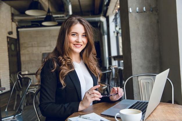 Donna di affari ampiamente sorridente che lavora al computer portatile che si siede in un caffè