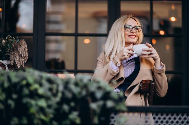 Donna di affari anziana in un cappotto che si siede fuori del caffè e che legge rivista