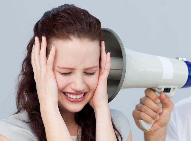 Donna di affari arrabbiata che ascolta un megafono