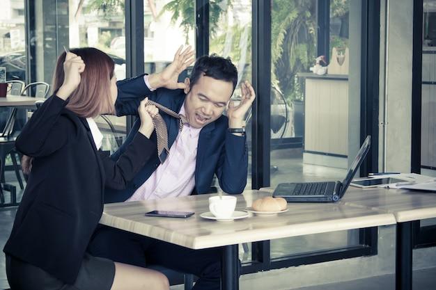 Donna di affari arrabbiata che grida ad un uomo d'affari in caffè