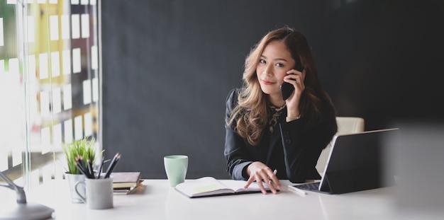 Donna di affari asiatica attraente che sorride e che osserva