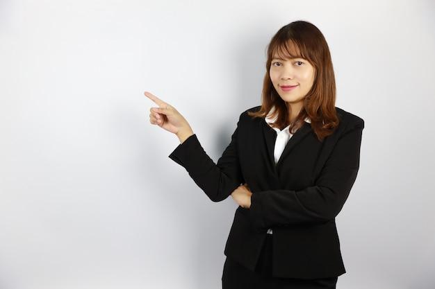Donna di affari asiatica che indica qualcosa con il fronte sorridente e sicuro su bianco