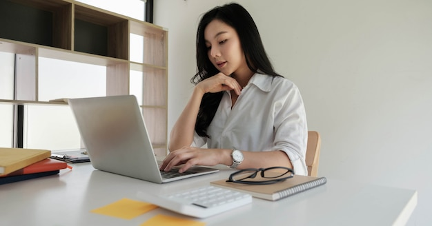 Donna di affari asiatica che lavora con il computer portatile portatile