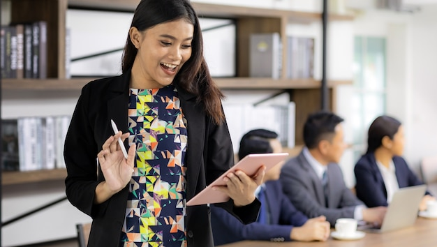 Donna di affari asiatica che lavora con la compressa intelligente