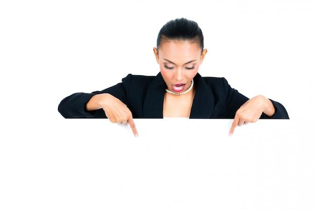 Donna di affari asiatica che mostra bordo bianco vuoto