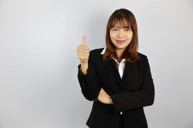 Donna di affari asiatica che mostra pollice in su con il fronte sorridente e sicuro su bianco