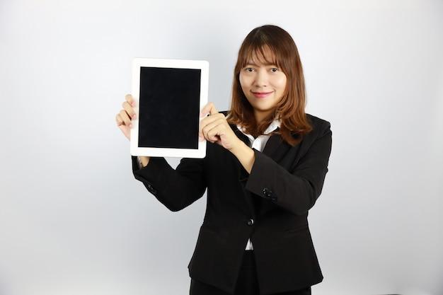 Donna di affari asiatica che mostra qualcosa mentre per mezzo della compressa su bianco