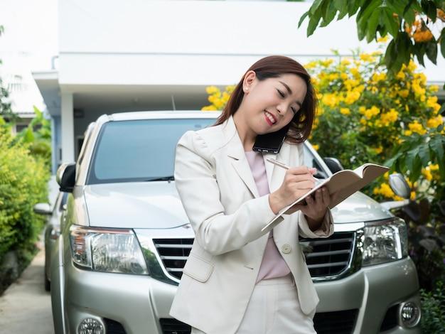 Donna di affari asiatica che parla sul telefono cellulare e che fa le note contro un'automobile.