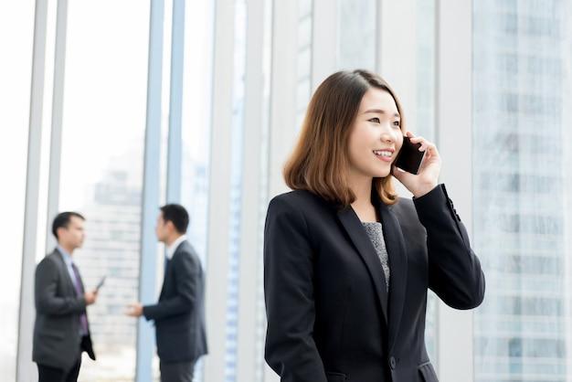 Donna di affari asiatica che parla sul telefono cellulare nel corridoio dell'edificio per uffici