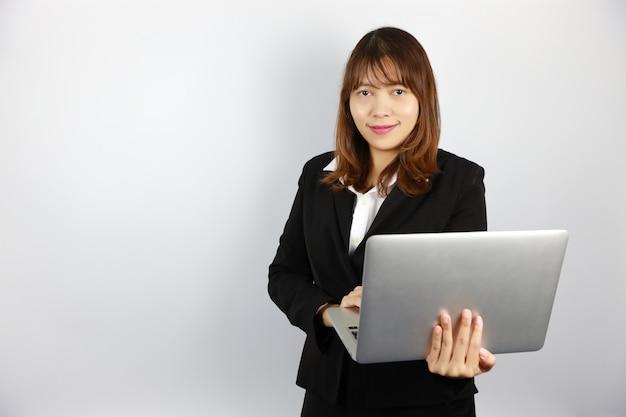 Donna di affari asiatica che per mezzo del computer con il fronte sorridente e sicuro su bianco