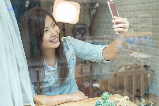 Donna di affari asiatica che prende il selfie con azione di felicità in caffetteria moderna