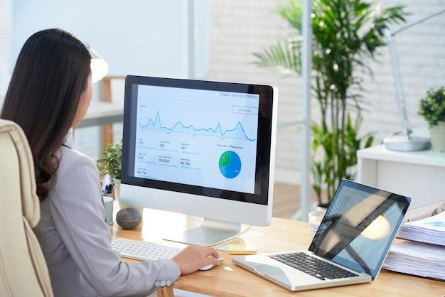 Donna di affari asiatica che si siede allo scrittorio in ufficio e che studia i grafici sullo schermo di grande computer