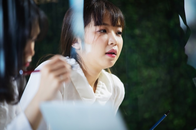 Donna di affari asiatica che spiega qualcosa al suo collega