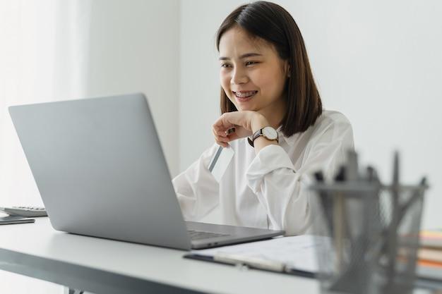 Donna di affari asiatica che utilizza computer portatile sulla tavola nell'ufficio.