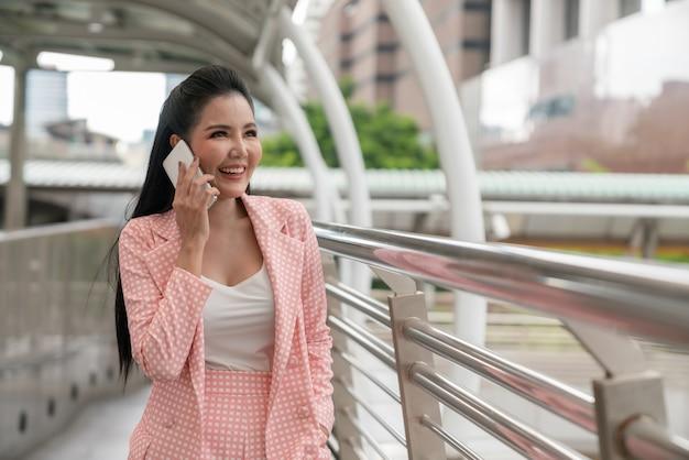 Donna di affari asiatica felice che sorride e che rivolge allo smartphone mentre camminando sulla via della città