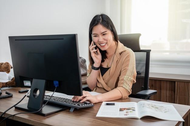 Donna di affari asiatica in vestito convenzionale che scrive e che lavora con il computer e cellulare in ufficio