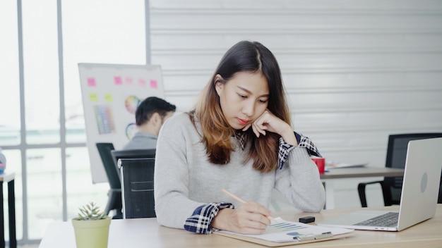 Donna di affari asiatica professionale che lavora al suo ufficio tramite computer portatile.