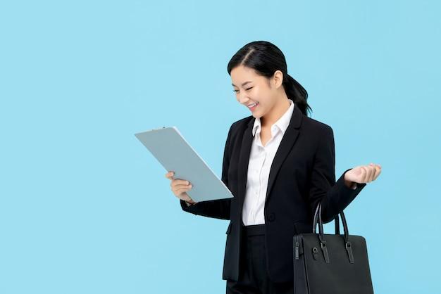 Donna di affari asiatica professionale in vestito convenzionale che esamina lavagna per appunti