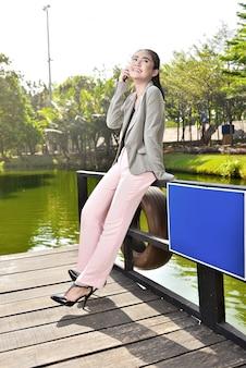 Donna di affari asiatica sorridente che comunica sul telefono mentre distendendosi