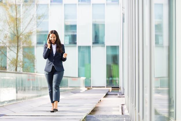 Donna di affari asiatica sorridente che parla sullo smartphone