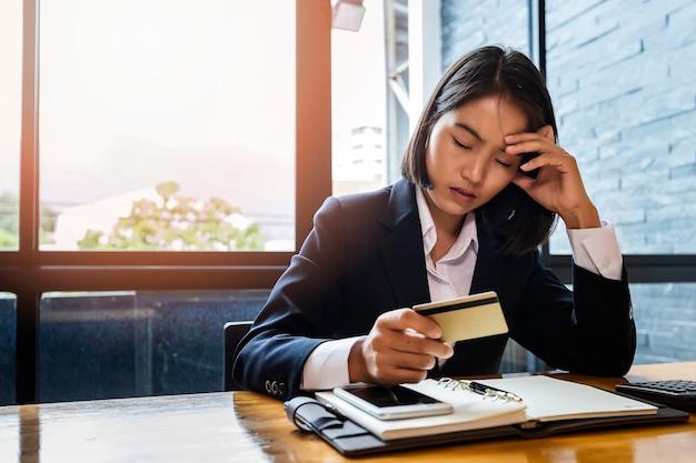 Donna di affari asiatica stressante con enorme quantità di debito della carta di credito