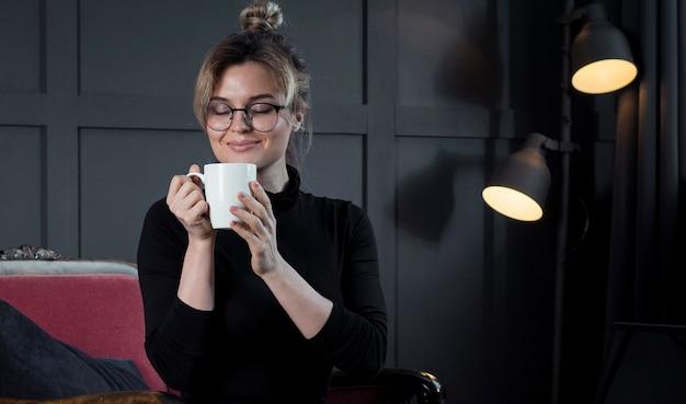 Donna di affari astuta che mangia una tazza di caffè
